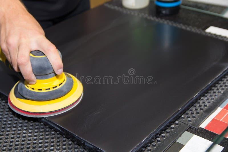 La mano del trabajador es una máquina pulidora foto de archivo libre de regalías