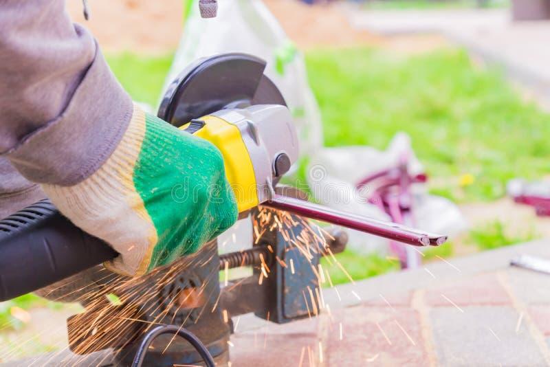 La mano del trabajador que corta el metal con la amoladora Chispea mientras que muele el hierro imágenes de archivo libres de regalías
