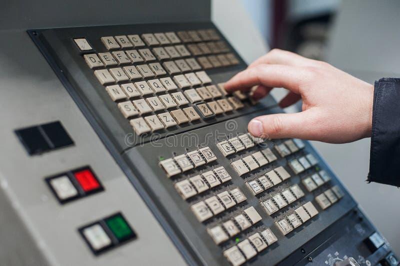 La mano del uso del operador da vuelta a control del interruptor del dial en el panel para ajusta el parámetro de la máquina del  imagen de archivo libre de regalías