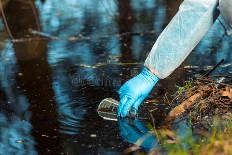la mano dell'ecologo del primo piano di un ricercatore, produce un processo di prelievo del campione dell'acqua immagine stock libera da diritti