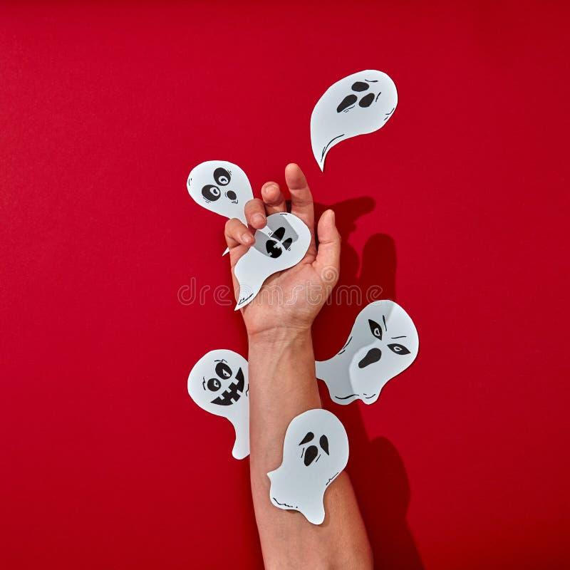 La mano dell'uomo è decorata con carta handcraft i fantasmi spaventosi di carta su un fondo rosso con lo spazio della copia Hallo fotografia stock