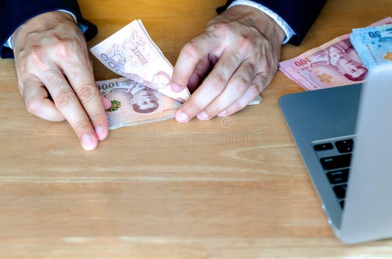 La mano dell'uomo che conta nuovi soldi tailandesi una banconota da 1.000 baht immagine stock