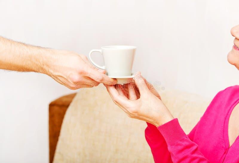 La mano dell'uomo che dà tazza di tè o di caffè alla donna senior fotografie stock libere da diritti