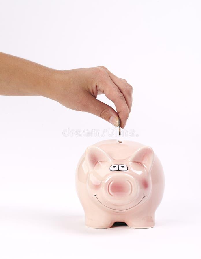 La mano dell'uomo che inserisce moneta nel porcellino salvadanaio fotografia stock