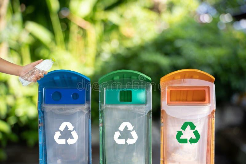 la mano dell'uomo che mette la riutilizzazione di plastica per il riciclaggio del mondo di protezione dell'ambiente di concetto r fotografia stock libera da diritti