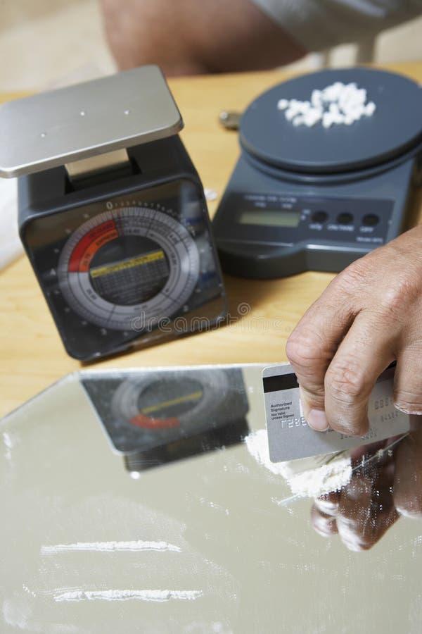 La mano dell'uomo che prepara le linee della cocaina con la carta di credito sullo specchio immagini stock