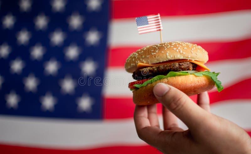 La mano dell'uomo che tiene un hamburger con i precedenti della bandiera americana immagini stock