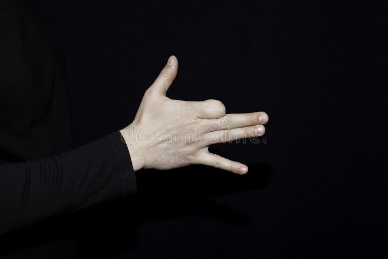 La mano dell'uomo come cane dipende il backround scuro immagine stock libera da diritti