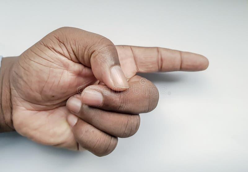 La mano dell'uomo con l'indice che indica a qualcosa nella direzione sinistra immagini stock