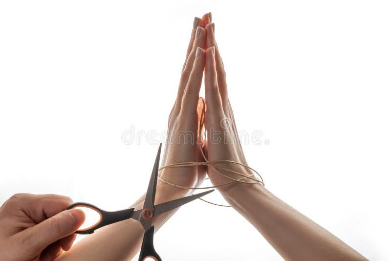La mano dell'uomo con le forbici nere sta tagliando la corda che cosa sta tenendo le mani femminili sui precedenti bianchi Giorno immagini stock libere da diritti
