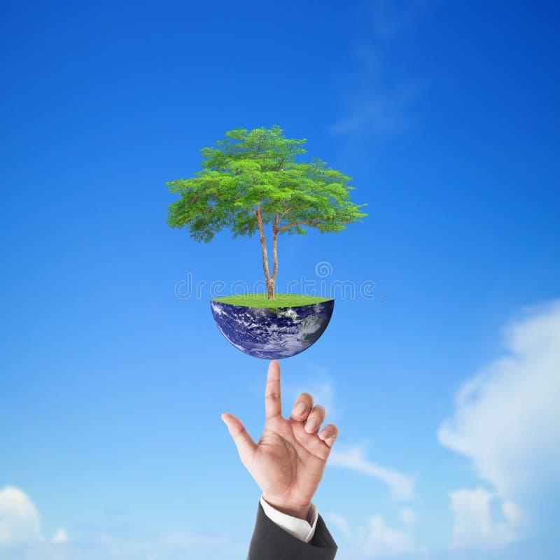 La mano dell'uomo d'affari che tiene il grande albero sulla terra con cielo blu, elementi di questa immagine è fornita dalla NASA fotografia stock libera da diritti