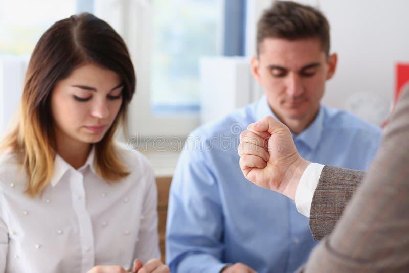 La mano dell'uomo d'affari minaccia i suoi impiegati impiegati immagine stock