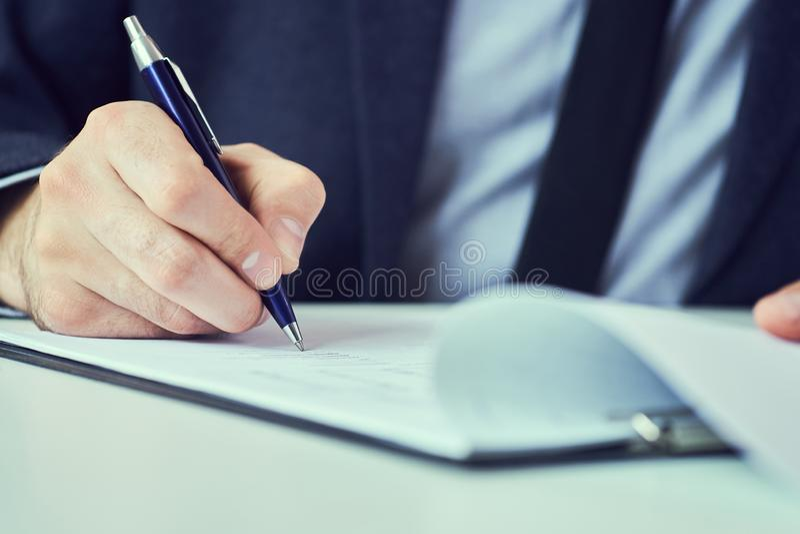 La mano dell'uomo d'affari nel riempimento del vestito e nella forma di firma di accordo di associazione ha tagliato per riempire immagine stock