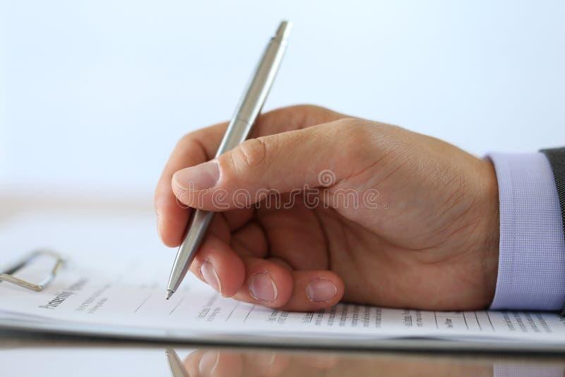 La mano dell'uomo d'affari nell'associazione di riempimento e di firma del vestito acconsente immagine stock libera da diritti