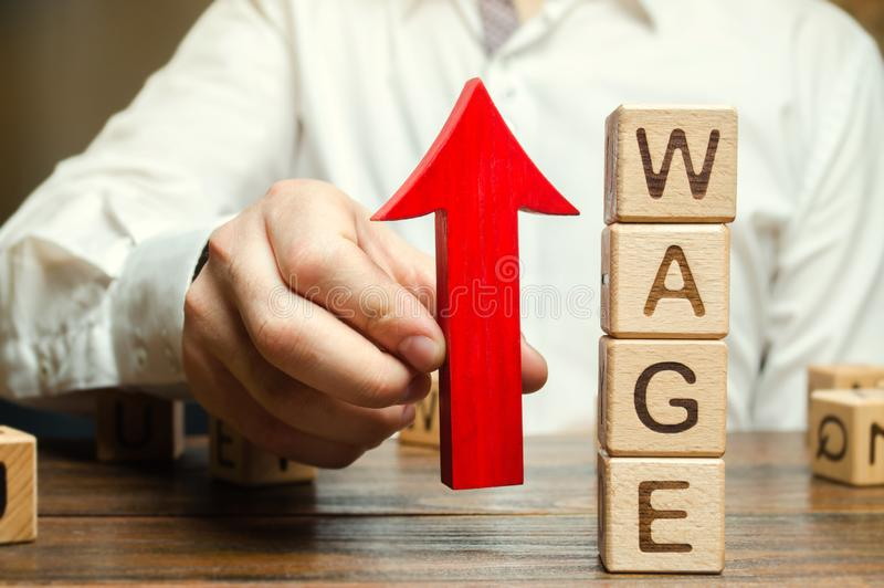 La mano dell'uomo d'affari tiene la freccia rossa su vicino ai blocchi di legno con lo stipendio di parola Concetto di aumento di fotografie stock libere da diritti