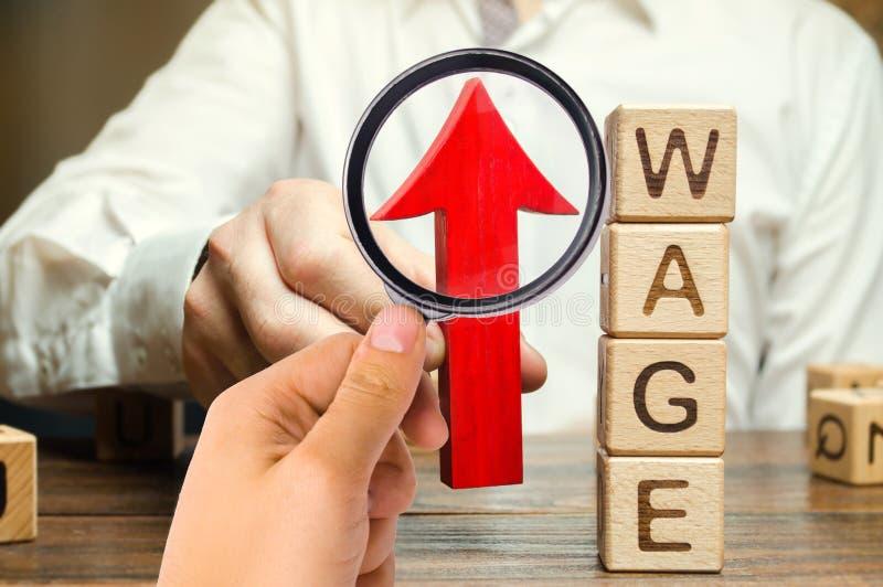 La mano dell'uomo d'affari tiene la freccia rossa su vicino ai blocchi di legno con lo stipendio di parola Concetto di aumento di fotografia stock