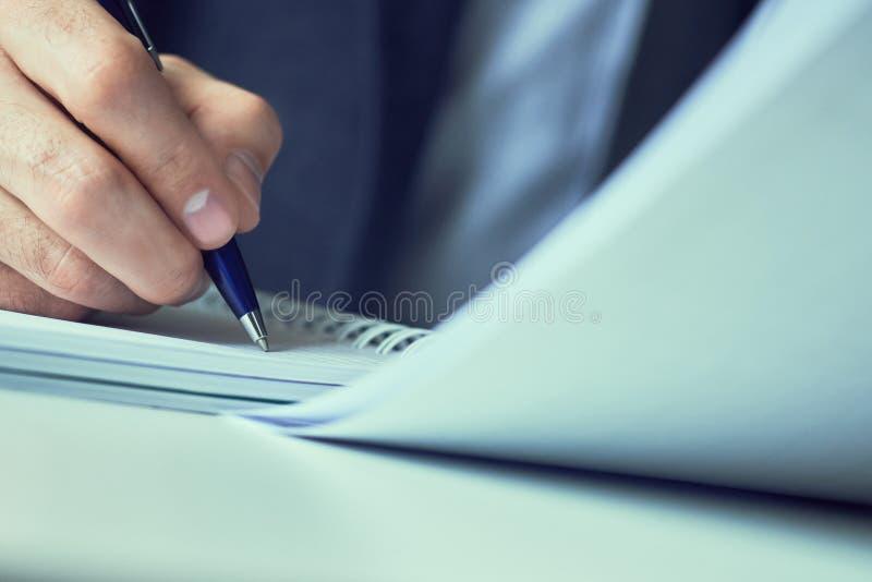La mano dell'uomo d'affari in vestito che riempie e che firma con la forma blu di accordo di associazione della penna ha tagliato immagine stock libera da diritti