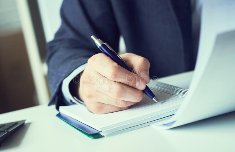 La mano dell'uomo d'affari in vestito che riempie e che firma con la forma blu di accordo di associazione della penna ha tagliato fotografia stock