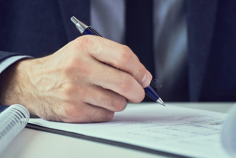 La mano dell'uomo d'affari in vestito che riempie e che firma con la forma blu di accordo di associazione della penna ha tagliato fotografie stock libere da diritti