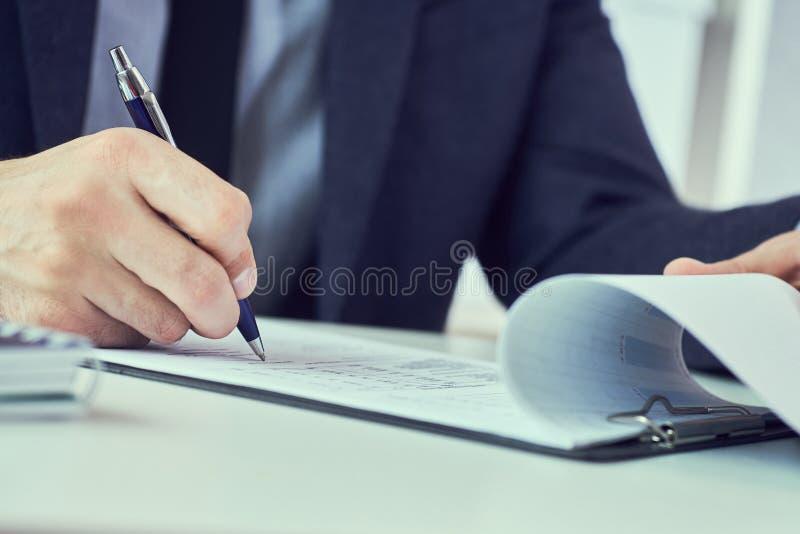 La mano dell'uomo d'affari in vestito che riempie e che firma con la forma blu di accordo di associazione della penna ha tagliato immagini stock libere da diritti