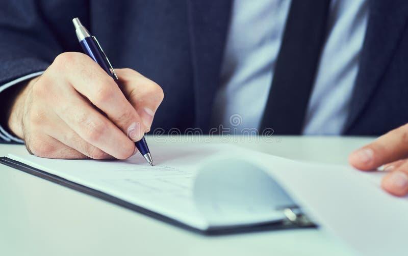 La mano dell'uomo d'affari in vestito che riempie e che firma con la forma blu di accordo di associazione della penna ha tagliato immagini stock