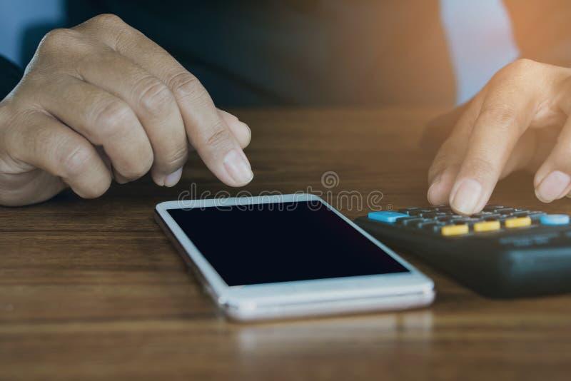 La mano dell'uomo di affari che calcola le sue spese mensili durante la tassa condisce immagine stock