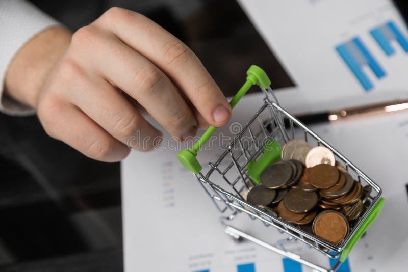 La mano dell'uomo giudica un carrello fittizio riempito di monete fotografie stock