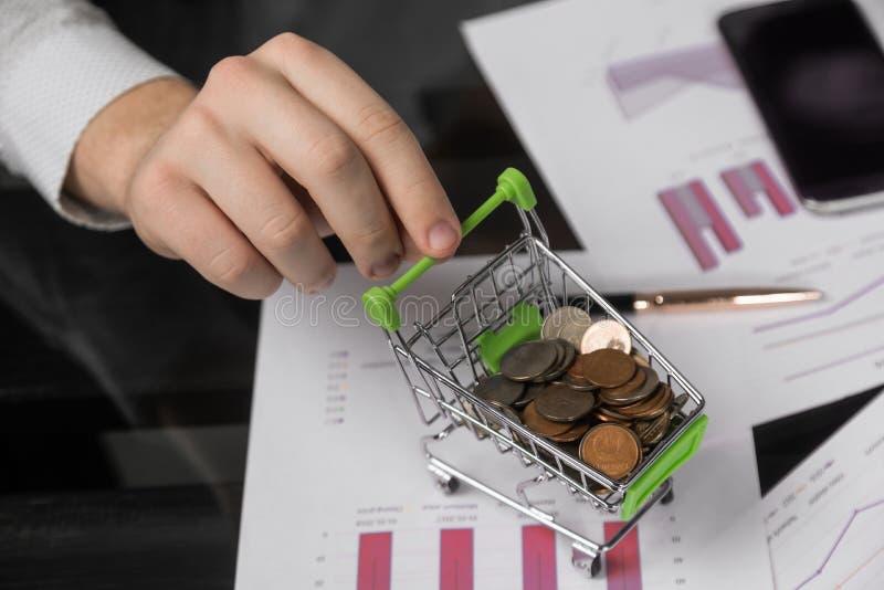 La mano dell'uomo giudica un carrello fittizio riempito di monete fotografia stock