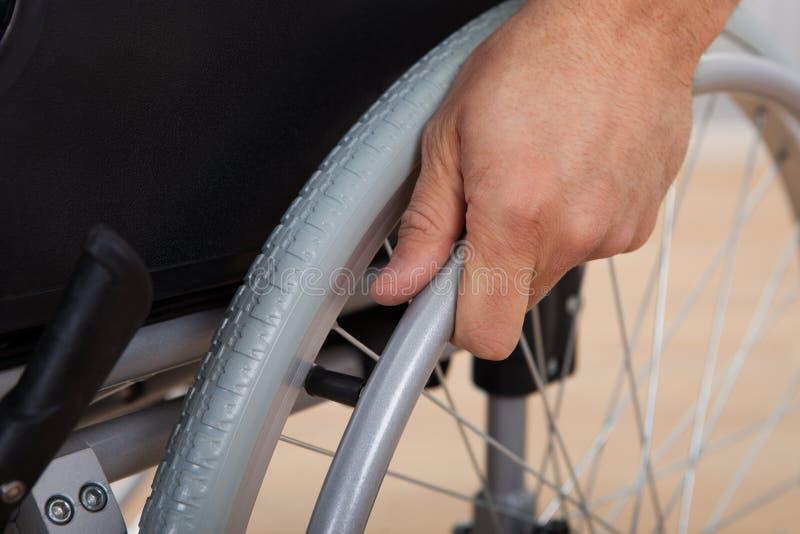 La mano dell'uomo handicappato che spinge ruota della sedia a rotelle fotografia stock