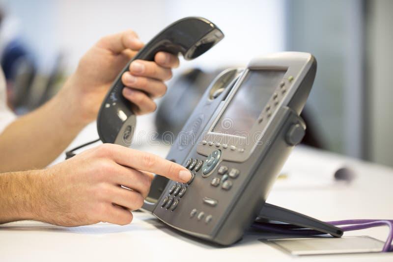 La mano dell'uomo sta componendo un numero di telefono, fondo dell'ufficio immagine stock libera da diritti