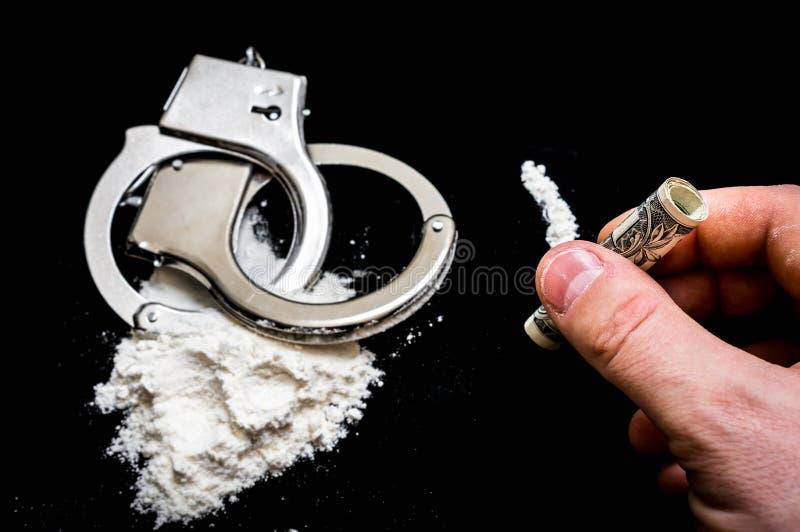 La mano dell'uomo tiene la banconota rotolata per sniffare la cocaina immagine stock libera da diritti