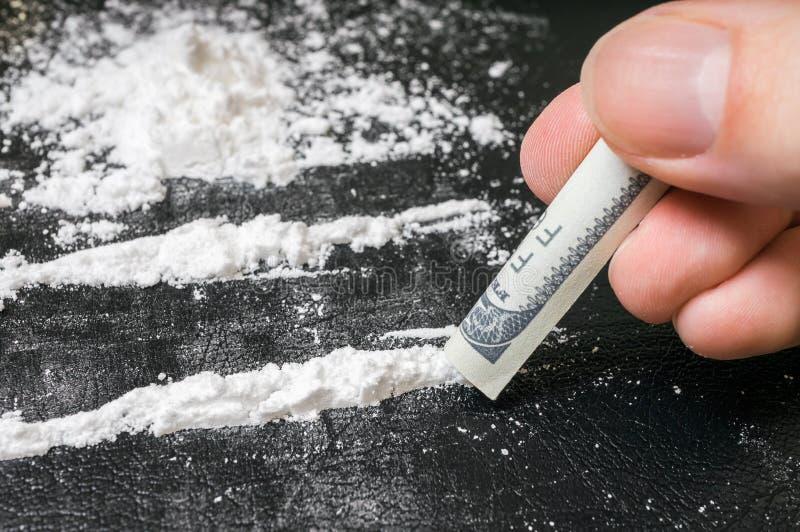 La mano dell'uomo tiene la banconota rotolata per sniffare la polvere della cocaina fotografia stock