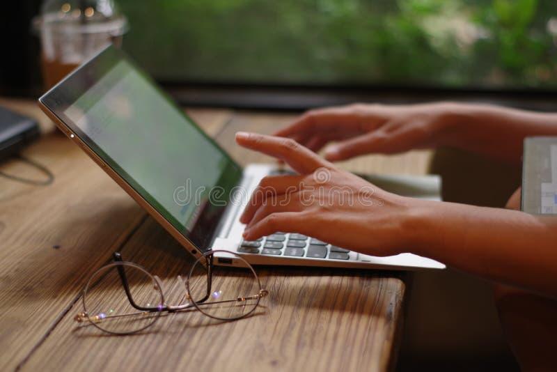 La mano della donna che lavora al computer portatile della tastiera sulla tavola di legno in un caffè immagini stock libere da diritti