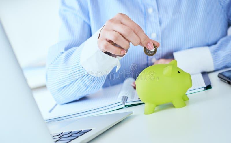 La mano della donna che mette la moneta dei soldi in primo piano verde del porcellino salvadanaio nel fondo dell'ufficio Affare c immagine stock libera da diritti
