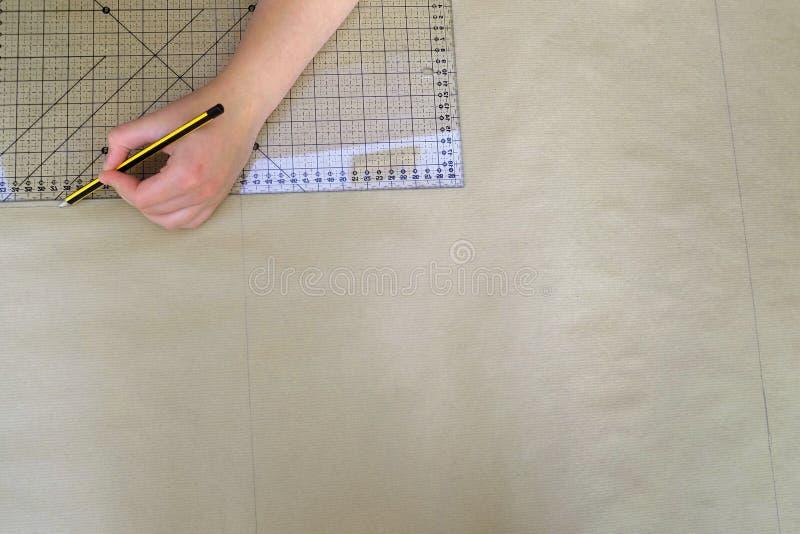 La mano della donna che misura e che attinge la carta kraft marrone fotografie stock