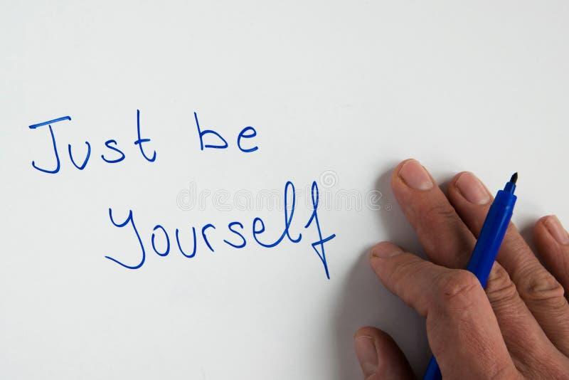 La mano della donna che scrive il ` motivazionale di frase crede appena il ` fotografie stock