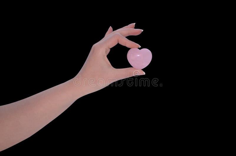 La mano della donna che tiene il cuore di Rose Quartz immagini stock libere da diritti