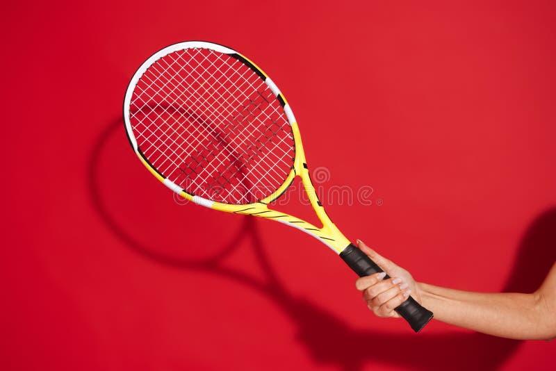 La mano della donna che tiene la racchetta di tennis sopra rosso fotografie stock