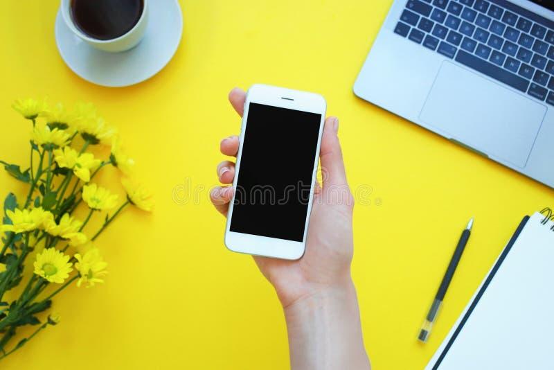 La mano della donna che tiene un telefono all'ufficio della tavola Fondo giallo fotografia stock libera da diritti