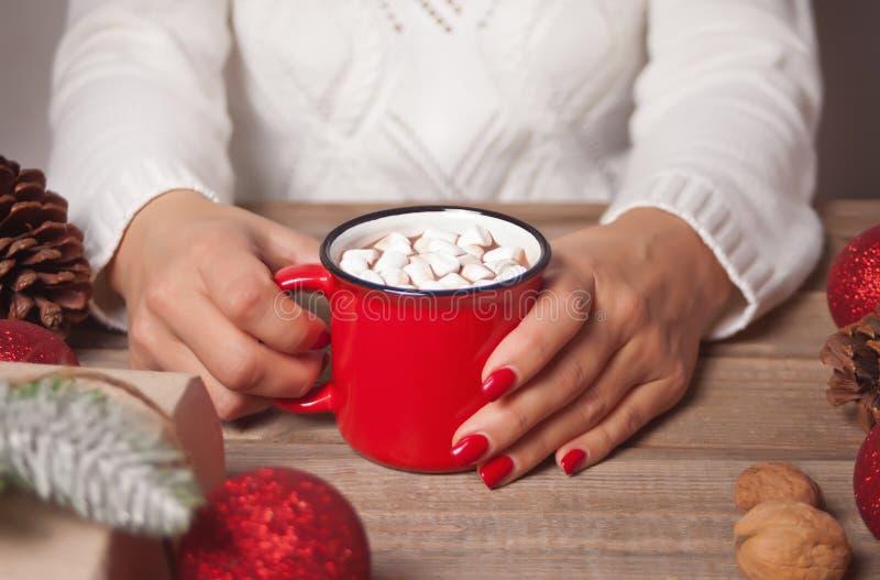La mano della donna che tiene una tazza rossa di cacao natalizio con marshmallows Le decorazioni natalizie sullo sfondo fotografia stock libera da diritti