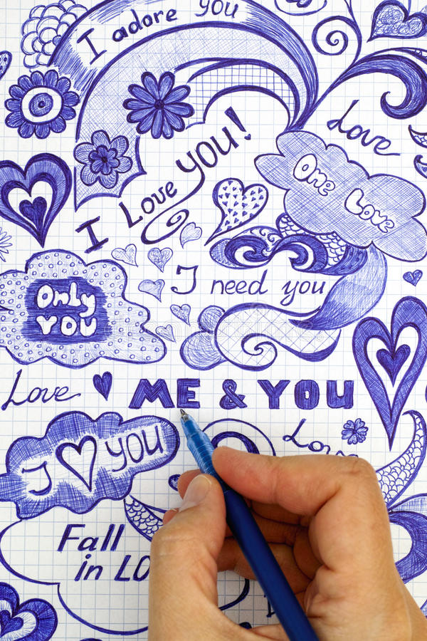 La mano della donna con la penna a sfera disegna i messaggi di scarabocchi di amore fotografie stock