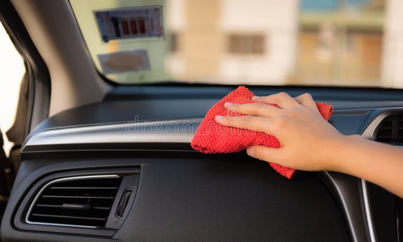 La mano della donna del primo piano è lavante e pulente con il microfiber al pannello di console dentro un'automobile , Servizio  immagini stock