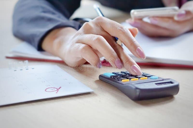 la mano della donna di affari che calcola le sue spese mensili durante la tassa condisce fotografia stock libera da diritti