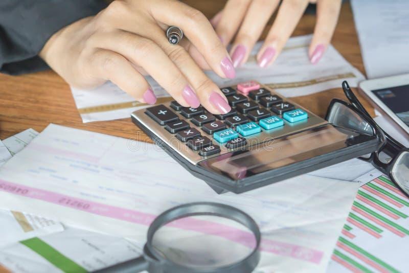 la mano della donna di affari che calcola le sue spese mensili durante la tassa condisce con alcune fatture fotografie stock