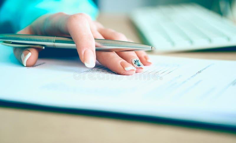 La mano della donna di affari che riempie e che firma con la forma d'argento di accordo di associazione della penna ha tagliato p fotografie stock
