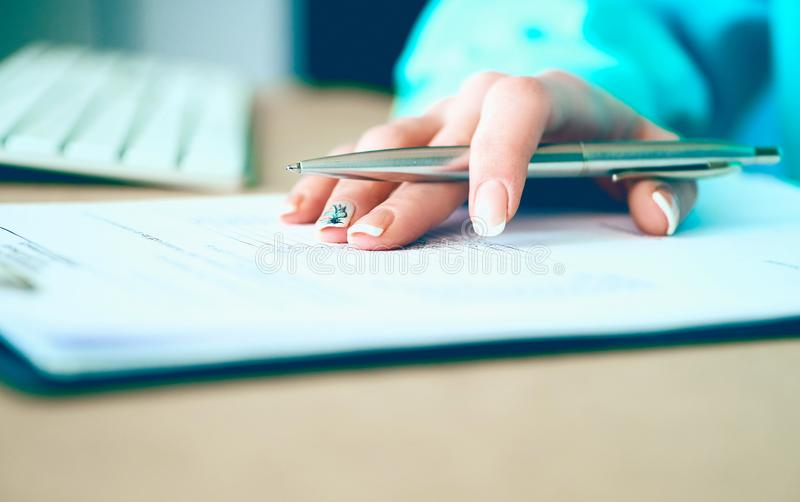 La mano della donna di affari che riempie e che firma con la forma d'argento di accordo di associazione della penna ha tagliato p immagine stock libera da diritti