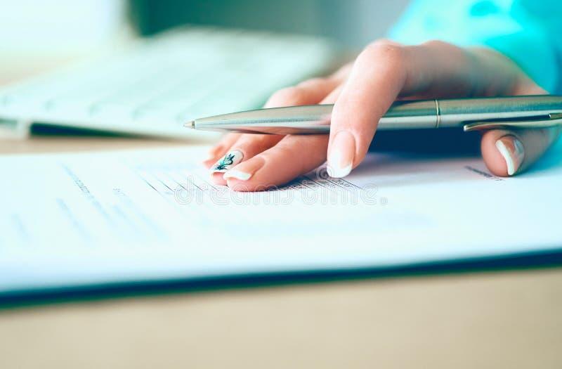 La mano della donna di affari che riempie e che firma con la forma d'argento di accordo di associazione della penna ha tagliato p fotografia stock