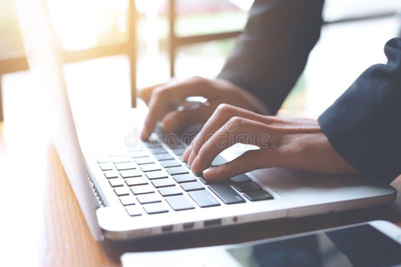 La mano della donna di affari sta lavorando ad un computer portatile in un ufficio immagine stock