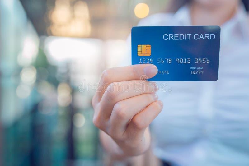 La mano della donna di affari tiene una carta di credito blu immagini stock