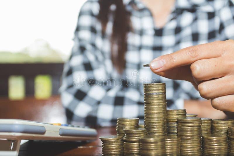 La mano della donna ha messo le monete per impilare delle monete, i soldi di risparmio per fut fotografia stock